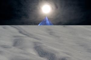 snow field with rising blue pyramid on horizon below sun on black sky