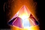 hyaline quartz pyramid burning in flame on black background lateral view